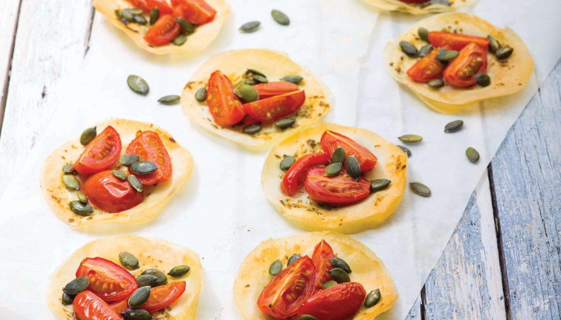 Minipiza de massa filo com tomate-chucha bebé, manjericão e sementes de abóbora