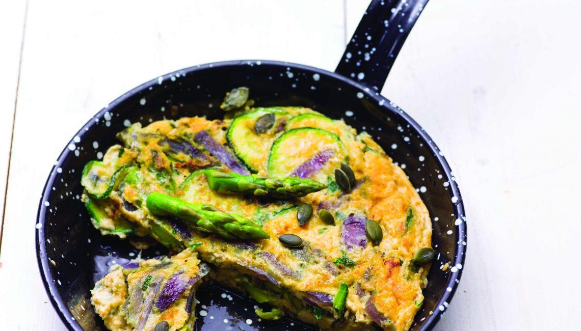 Tortilha de legumes saborosos com cebola roxa, sementes e ervas aromáticas